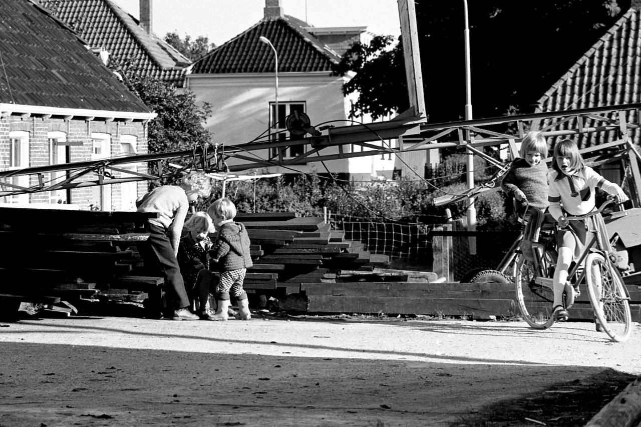 Spelende kinderen temidden van de houtopslag van de molen.