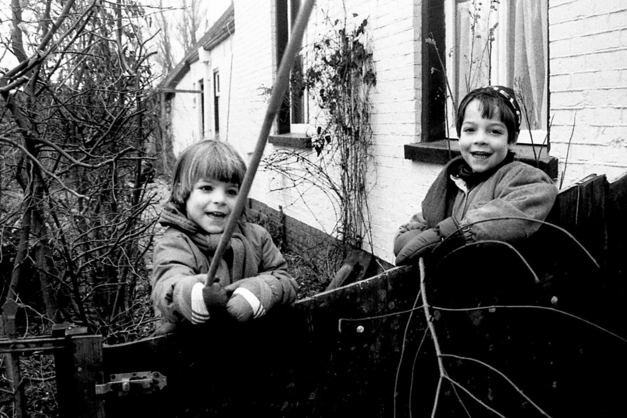 Zussen Eva en Roos aan de Meerstrakant van hun huis, ca. 1985