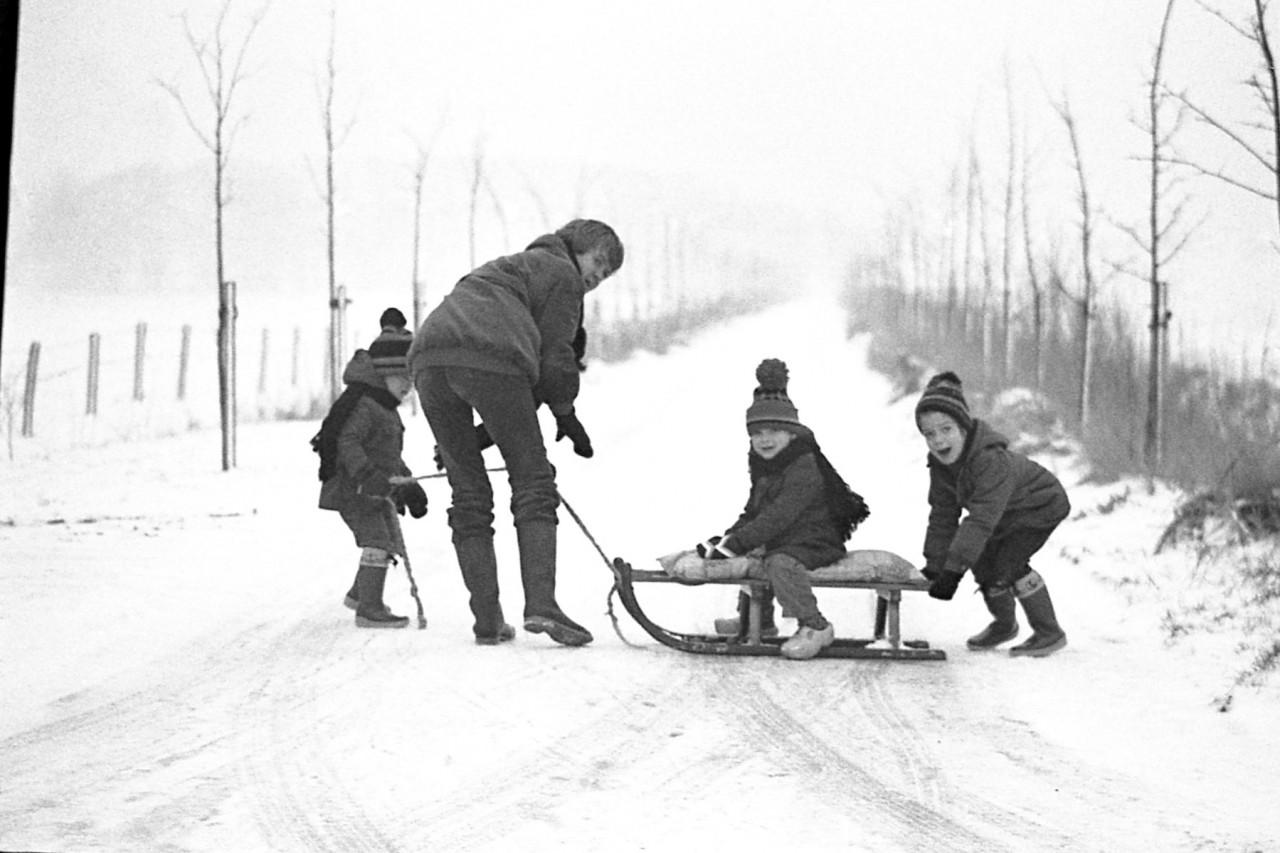 Moeder van Wijk haalt haar zoon Jasper met de slee en andere kinderen van de schoolbus af ca. 1980